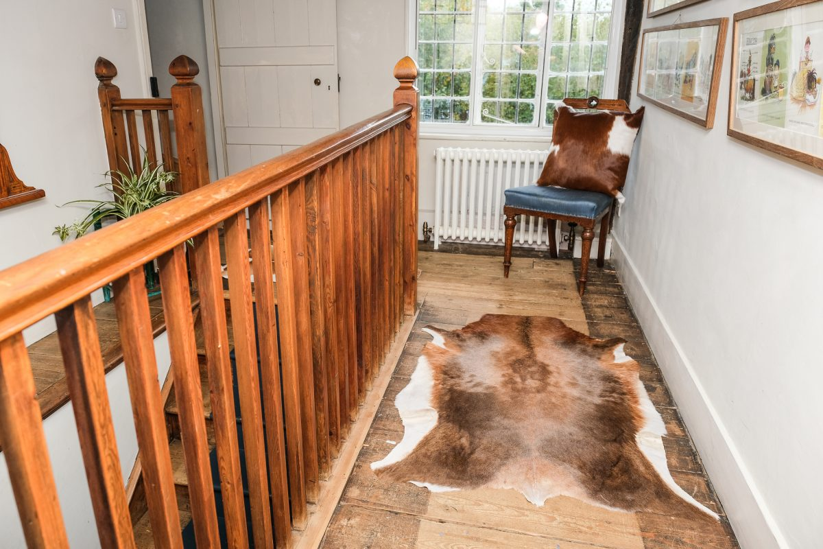 Small Brown and White Blesbok rug in hallway next to chair with Brown and White cowhide cusion