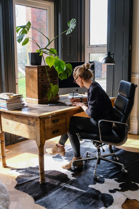 Women at desk in home office with Black and White cowhide rug underneath